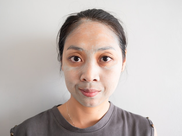 Unprofessional housewife woman applying green facial clay mask