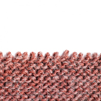 Unravelling knitted fabric on white