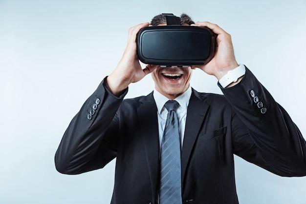 非現実的な感じ。口を大きく開けて背景に立ったまま興奮するvrメガネを使った楽しいビジネスマンの腰のショット。