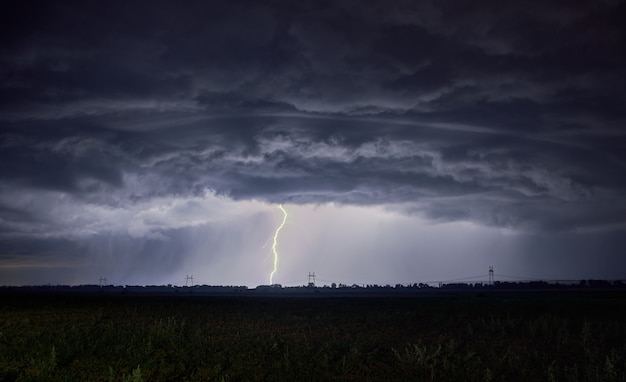 Unrealistically thick clouds and lightning strike into the ground Premium Photo