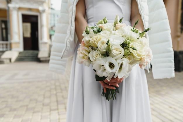 꽃다발을 들고 흰 드레스에 인식 할 수없는 신부를 닫습니다.