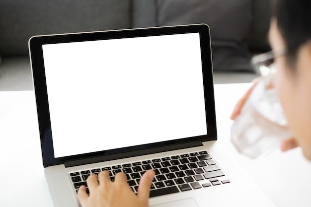 白のクリッピングパスで隔離された空の空白の画面でラップトップコンピューターの前で働いている認識できないアジアの若い男。空の白い画面の背景を持つモックアップラップトップコンピューター。