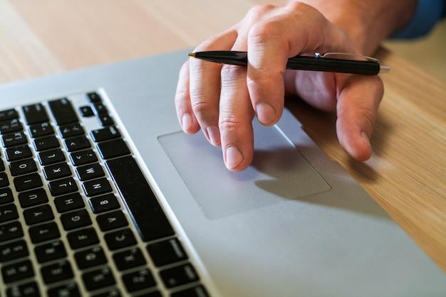 До неузнаваемости деловой человек печатает на ноутбуке