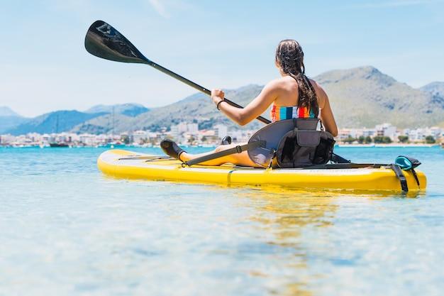 海のパドルボードを漕ぐ認識できない白人の女の子-コピースペース