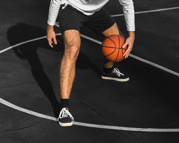 Неузнаваемый мужчина прыгает в баскетбол на корте