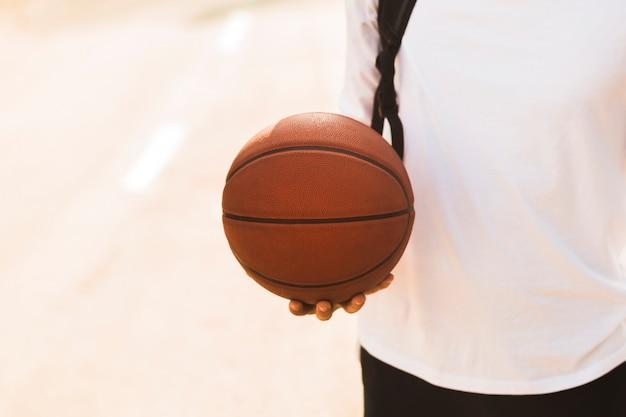バスケットボールの正面を保持している認識できない男