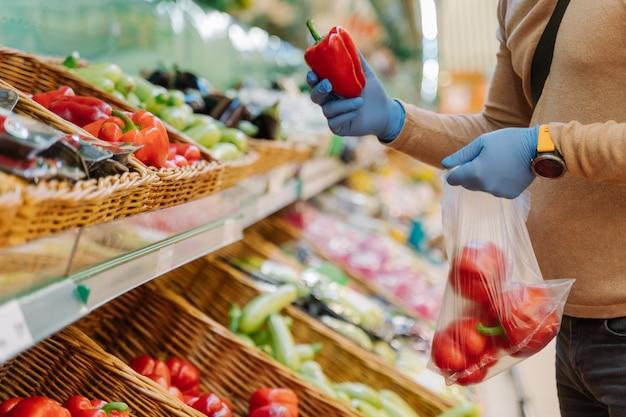 Неузнаваемый мужчина в резиновых защитных перчатках выбирает красный перец в супермаркете во время вспышки коронавирусной пневмонии