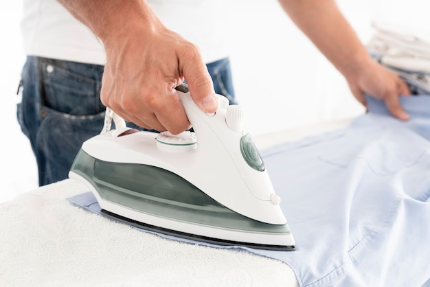 Unrecognisable man ironing clothes