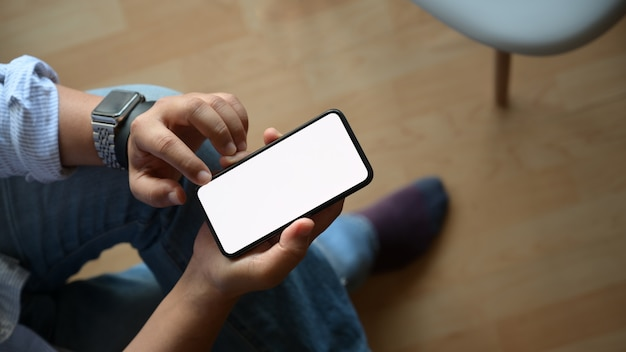 Unrecognisable man reading message on smart phone, blank screen mobile phone