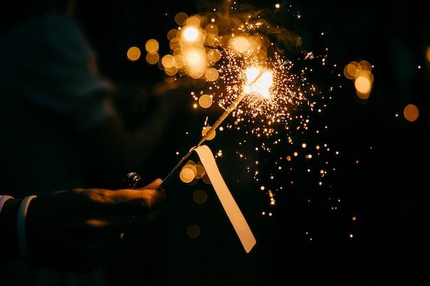 Неузнаваемый человек, держащий светящийся праздник, сверкающий рукой фейерверк, сияющий пламенем огня