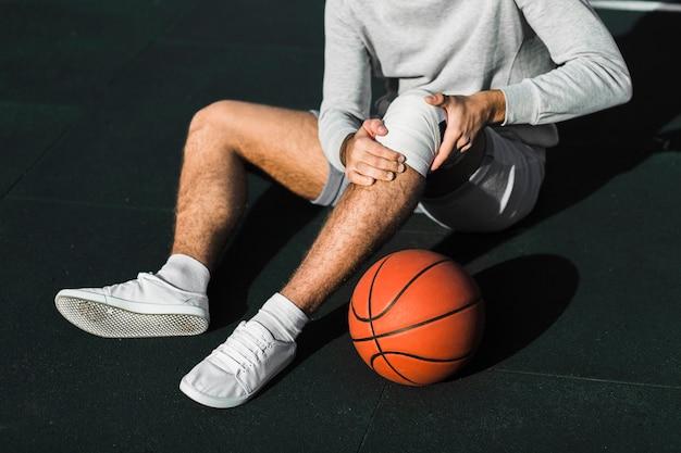 Giocatore irriconoscibile che applica fasciatura sul ginocchio