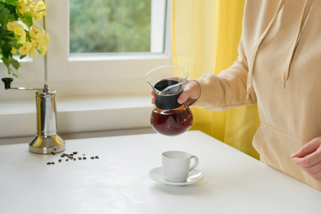 Unrecognisable woman pouring a coffee from glass coffee maker