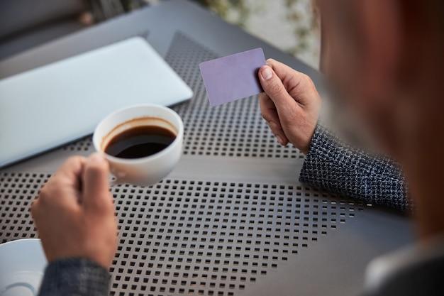 커피 한 잔과 빈 플라스틱 카드를 들고 인식 할 수없는 남자