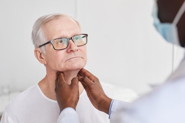 До неузнаваемости афро-американский врач пальпирует шею пожилого мужчины во время осмотра в больничной палате, копировальное пространство
