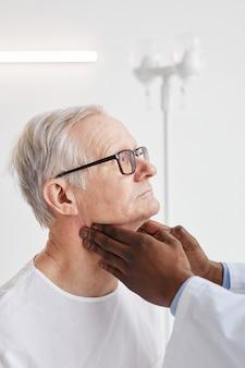 До неузнаваемости афро-американский врач пальпирует шею пожилого мужчины во время осмотра в больничной палате, вид сбоку