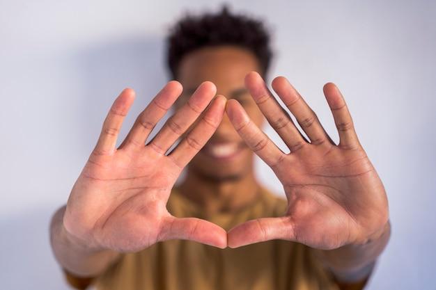 手で三角形の記号の形をしている認識できないアフリカ系アメリカ人の男。人種差別をやめ、異なる民族を受け入れます。大きく開いた両手のディテール。