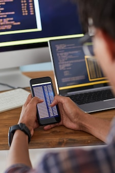Unrecognizable african-american man holding smartphone with code on screen while working at desk in office, it developer concept, copy space
