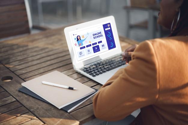 До неузнаваемости афро-американская женщина сидит за столом в уличном кафе и использует ноутбук
