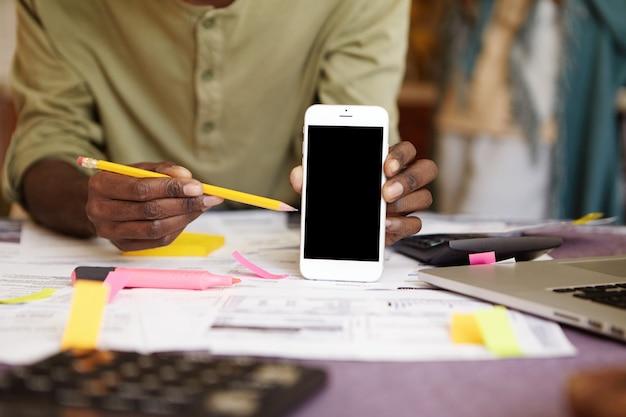 Uomo africano irriconoscibile che tiene la matita gialla, indicandolo allo smart phone dello schermo in bianco nella sua mano