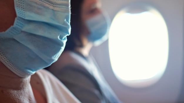 認識できない飛行機の乗客が医療用マスクで飛んでいます。
