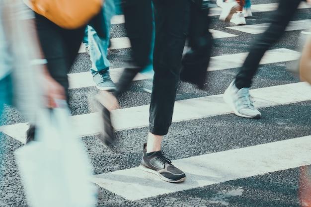 알아볼 수없고 흐릿한 사람들이 여름에 도시의 횡단 보도를 따라 걷습니다.