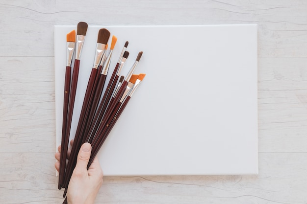 Unrecognizable artist holding paintbrushes and blank paper