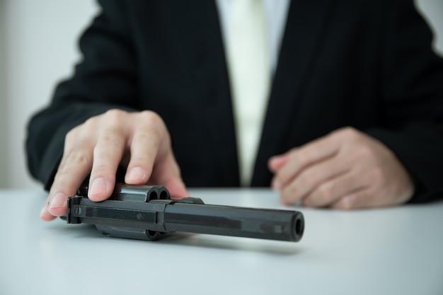 認識できないアジアのビジネスマンは、彼のスーツの中の銃ホルダーから銃をクローズアップで引き出します。テーブルの上にリボルバー拳銃を示す黒いスーツのビジネスマンまたはエージェント。