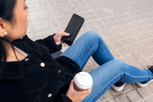 콘크리트 바닥에 야외에 앉아 전화를 타이핑하는 알아볼 수 없는 아시아 소녀