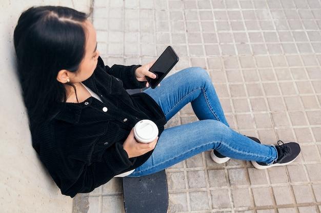 콘크리트 벽에 기대어 스케이트보드를 타고 야외에 앉아 전화를 타이핑하는 알아볼 수 없는 아시아 소녀