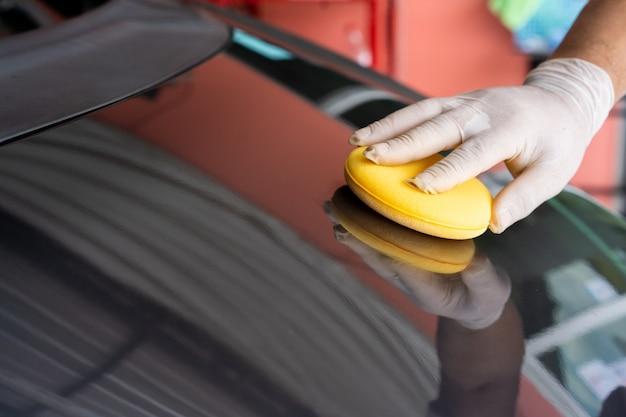 認識できないアジア人男性が、研磨スポンジを使用して車の外装を掃除し、こすります。カーワックス、オートケアコンセプトで車を磨くプロの労働者。