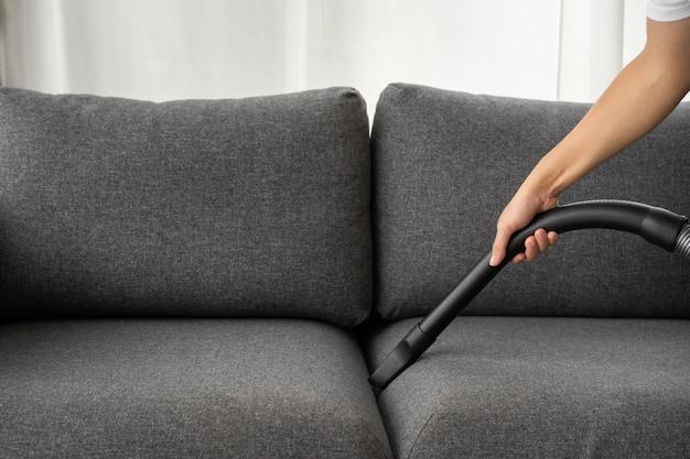 알아볼 수 없는 아시아 남자 가정부는 거실에 있는 소파에 있는 먼지를 진공 청소기로 청소하는 진공 기계를 사용합니다. 위생 생활을 위해 집을 청소하고 소독하는 남자. 진공 기계 및 가사