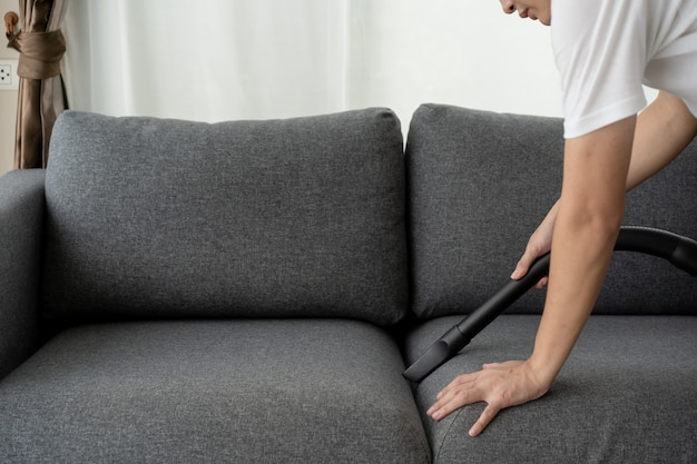 Unrecognizable asian man housekeeper using a vacuum machine vacuuming a dust on a sofa in living room close up. a man cleaning and sanitizing his house for hygiene living. vacuum machine and housework