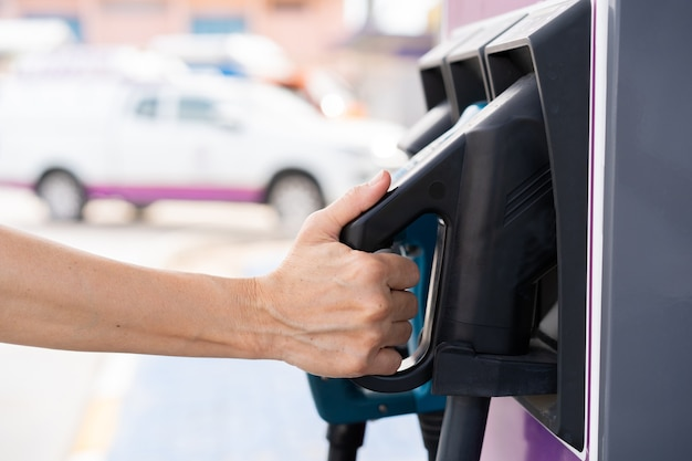 Unrecognizable asian woman holding aa dc - ccs type 2 ev charging connector at ev charging station, woman preparing an ev - electric vehicle charging connector for recharge a vehicle.