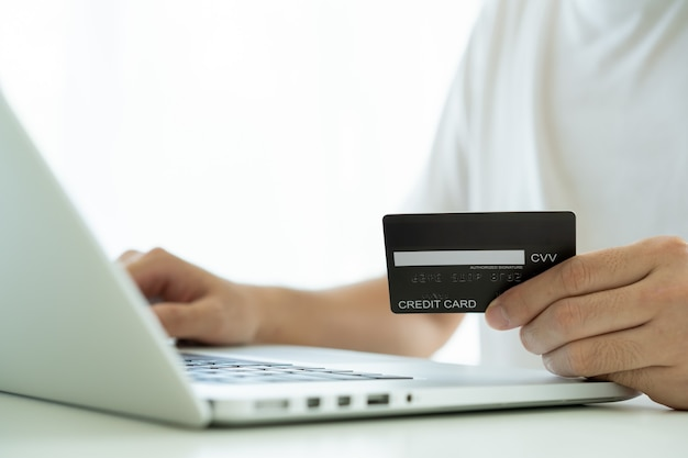 インターネットで購入するためにクレジットカードを使用している認識できないアジアの若い男。男性はオンライン決済でクレジットカードを使用します。 eコマースによる現代のショッピングライフスタイル。