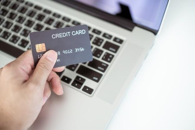 알아볼 수 없는 아시아 청년이 인터넷에서 신용 카드를 사용하여 구매합니다. 남자는 온라인 지불에 신용 카드를 사용합니다. 전자 상거래를 통한 현대적인 쇼핑 라이프 스타일.