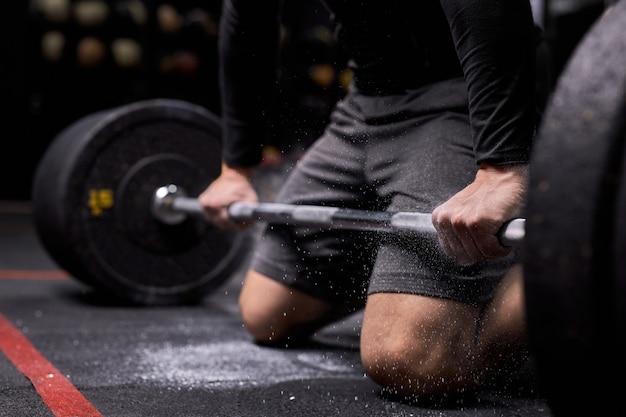 인식 할 수없는 운동 선수가 크로스 핏 훈련을 준비하고 있습니다. 무게 훈련을 준비하는 활석에 파워 리프터 손. 스포츠 및 피트니스 개념