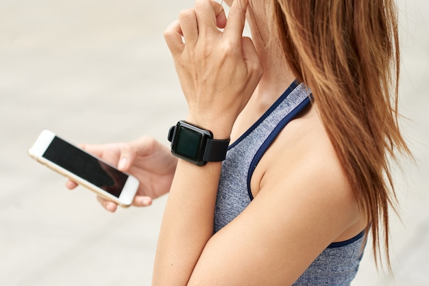 Unrecognizable athletic woman with smart watch checking pulse and using smartphone