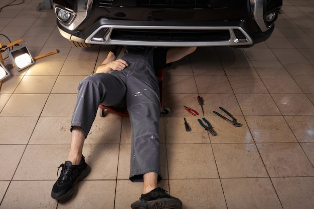 Unrecognizable auto mechanic lying and working under car