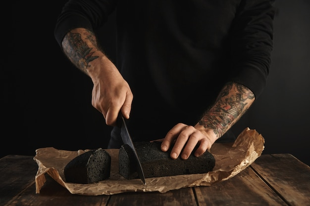 Unrecognizable baker with tattooed hands cut freshly baked homemade charcoal bread with big chief knife on slices on craft paper on wooden rustic table