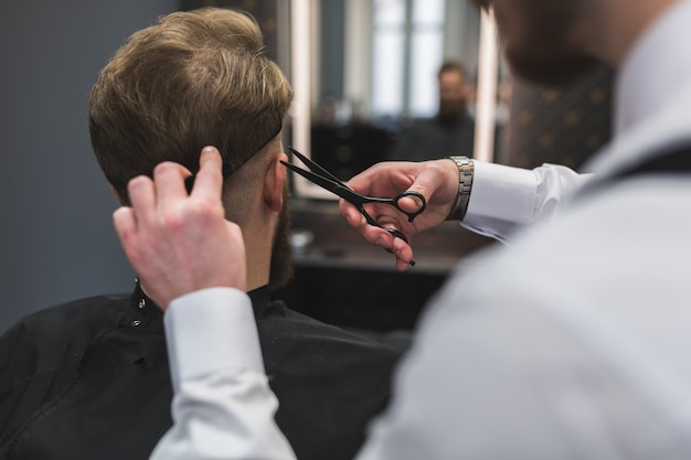 Unrecognizable barber and client