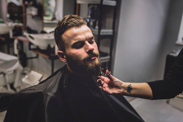 Unrecognizable barber cutting beard