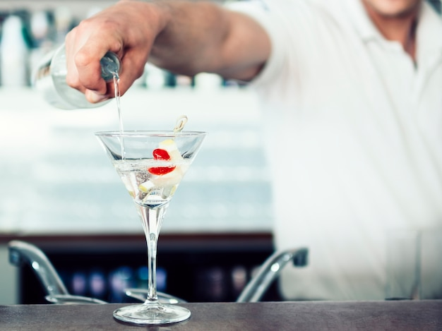 Unrecognizable barman pouring cocktail in glass
