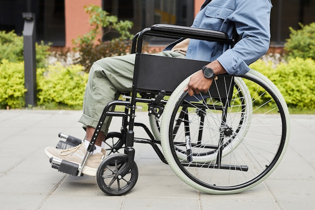 Unrecognizable black invalid in casual outfit holding wheelchairs handrails and pushing towards wheelchair outdoors
