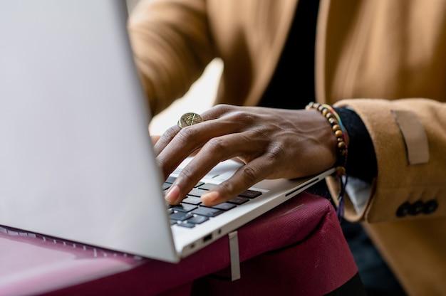 До неузнаваемости темнокожий мужчина печатает на клавиатуре ноутбука.