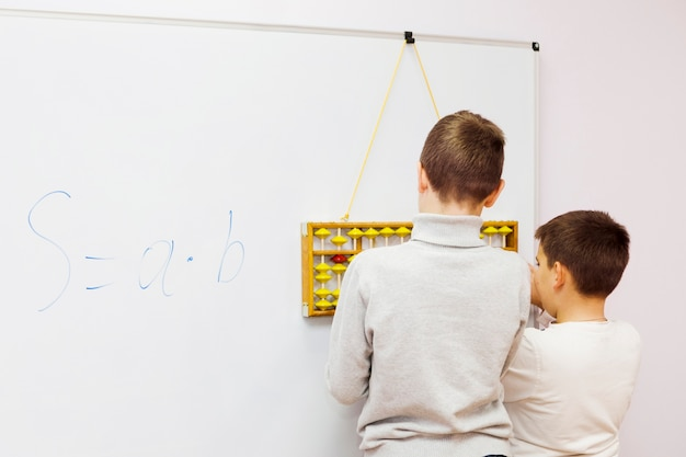 Unrecognizable boys using abacus near whiteboard