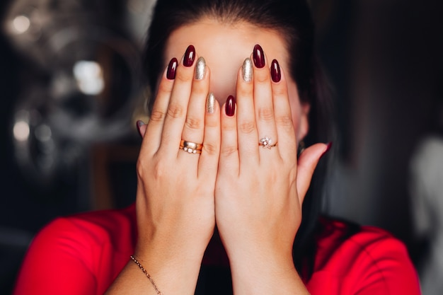 Unrecognizable brunette woman hiding her face with hands.