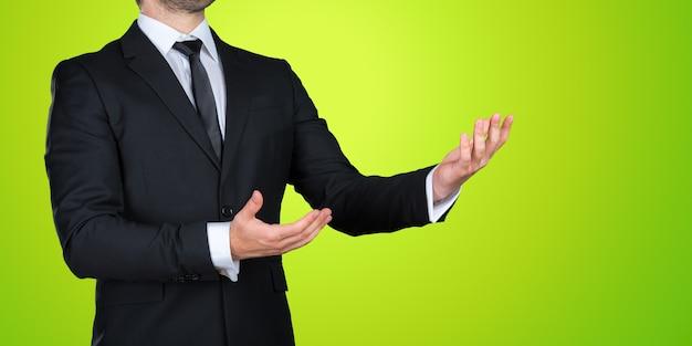 Unrecognizable businessman in a formal black suit presenting, showing copy space