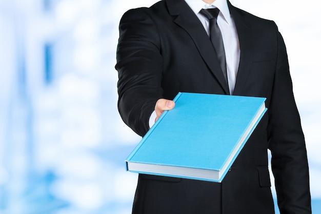 Unrecognizable businessman holding a book closeup