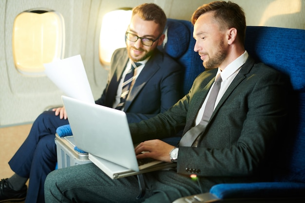 Unrecognizable businessman in plane