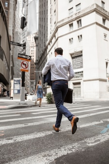 Unrecognizable businessman running on street
